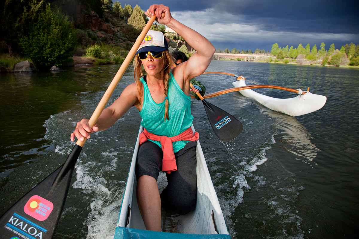 A beautiful paddler makes a stroke in an outrigger canoe race in the Deschuttes River in Bend Oregon