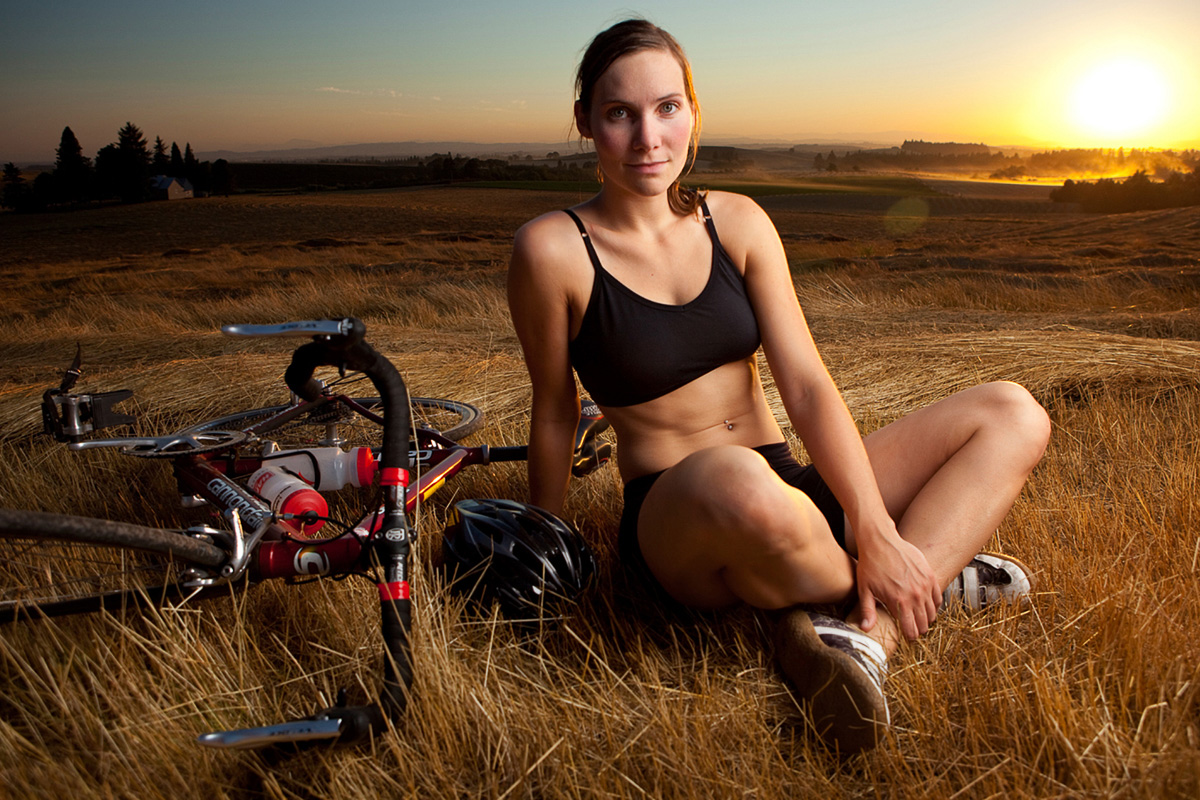 As the sun sets in the valley below a beautiful cyclist rests in a field.