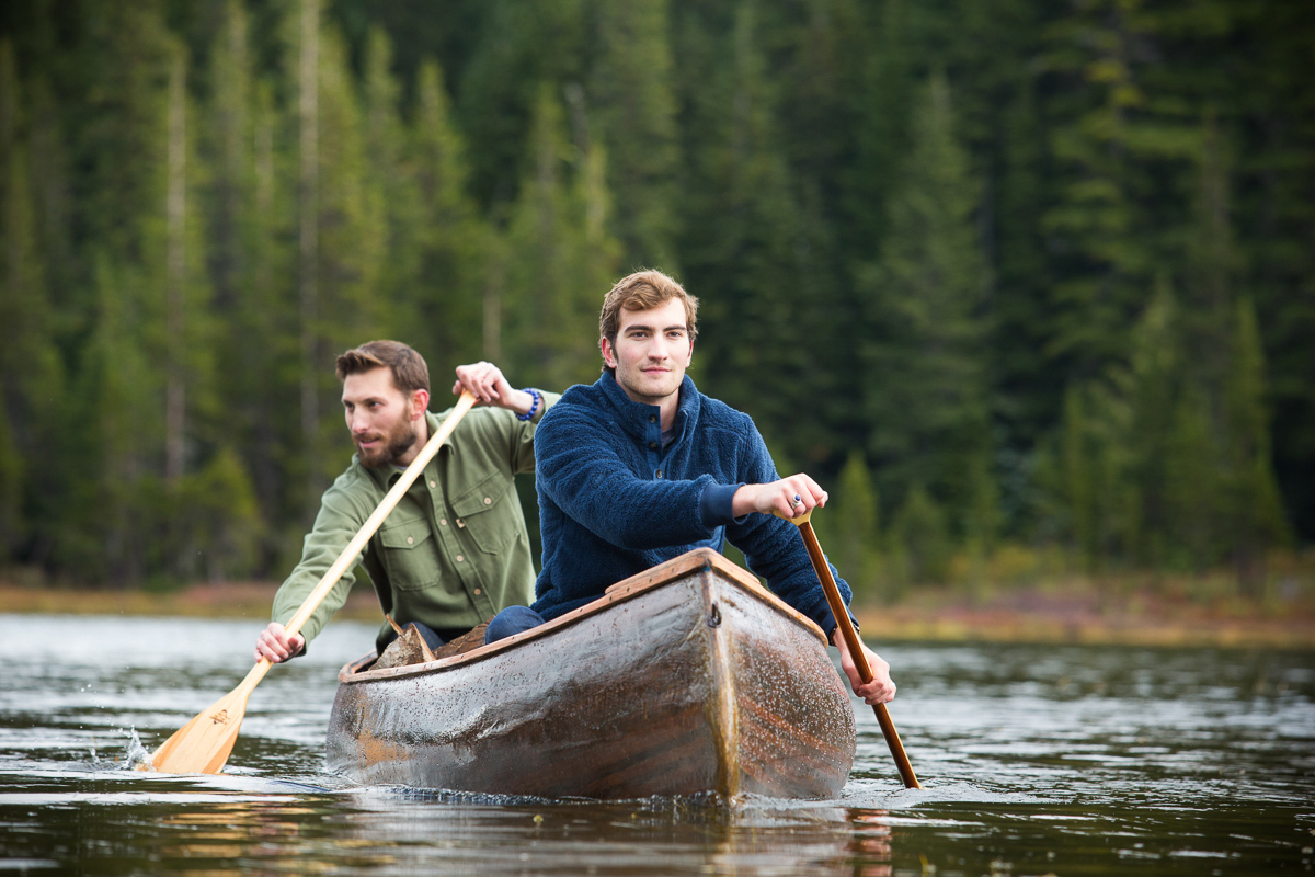 Two young men paddling a canoe on Oregon lake