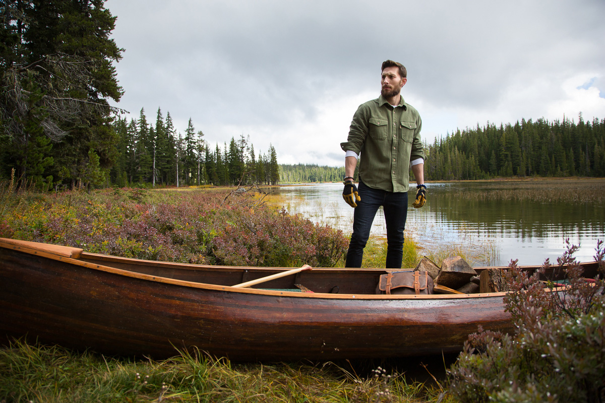 Young man by canoe and lake