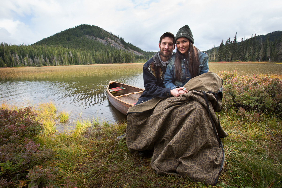 Young couple sitting on canoe with blanket