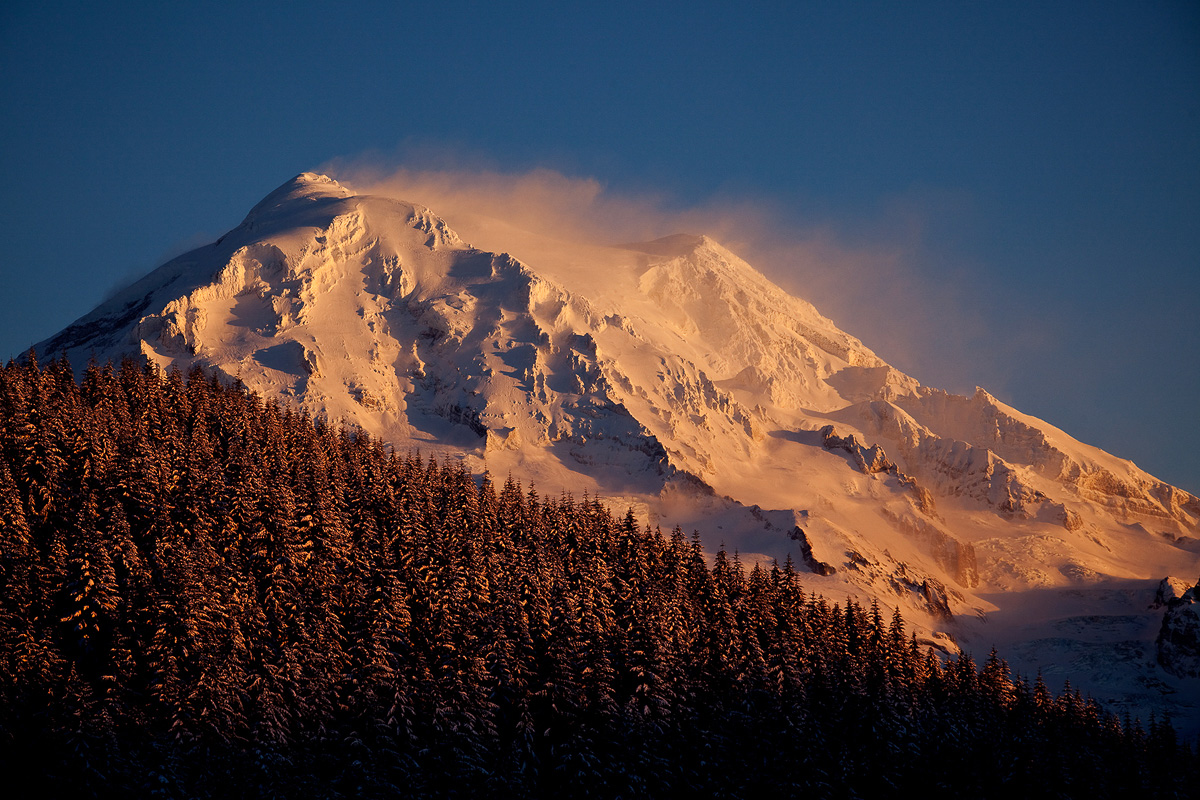 Raging wind blowing snow off the peak of Mt. Rainer in beautiful sunset light.