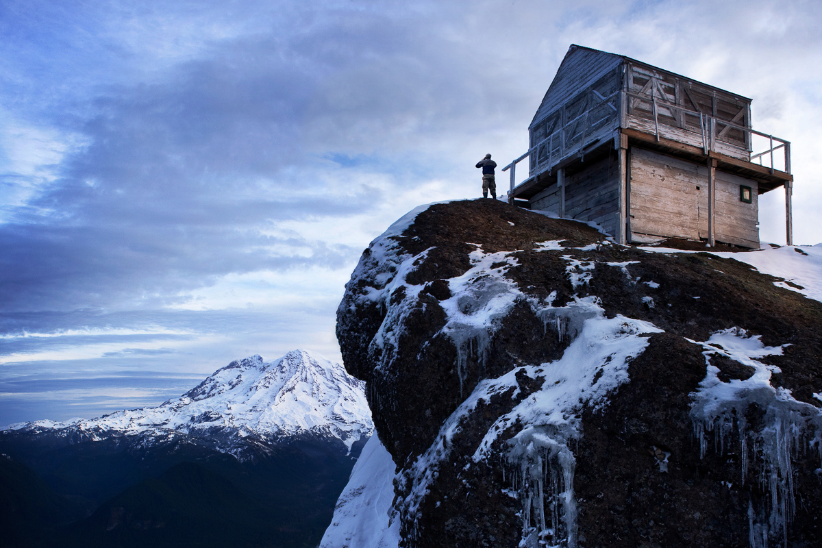 A man standing on an ice encrusted rock looking at Mt. Rainer form the high rocks lookout .