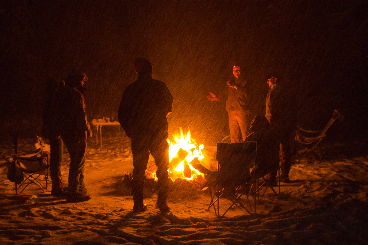 In a raging snowstorm friends stand around a blazing campfire telling stories.
