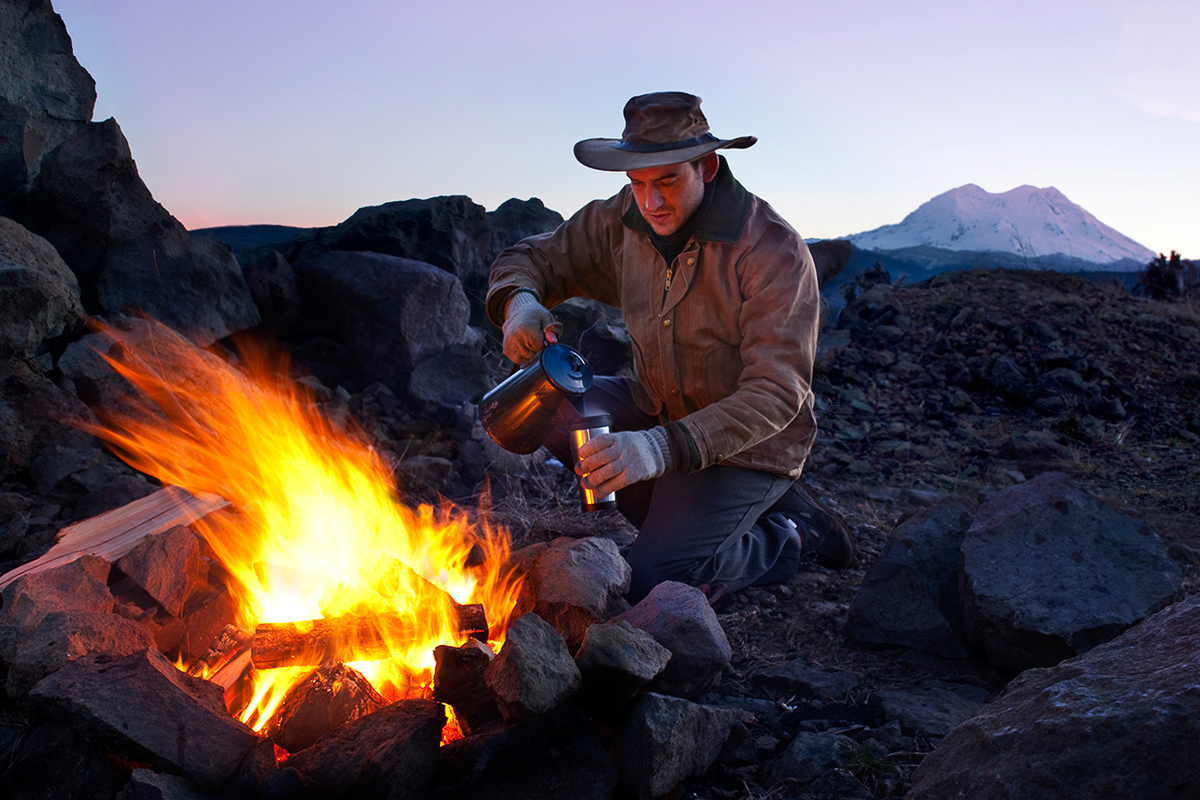 An outdoorsman pours a cup of hot coffee beside a blazing campfire with the sun rising over Mt.  Rainer in the background.