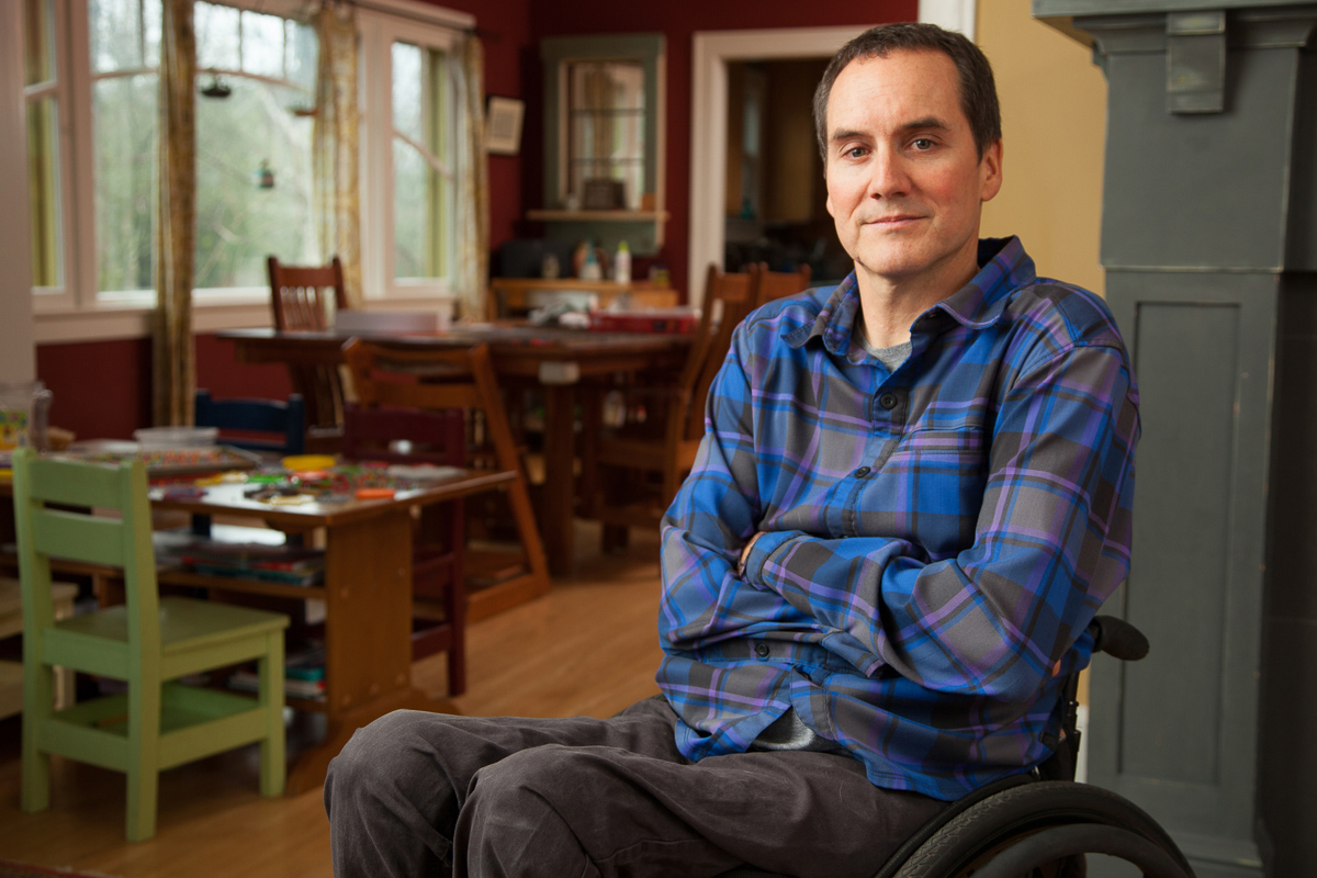 middle aged man sit in a wheelchair in his home
