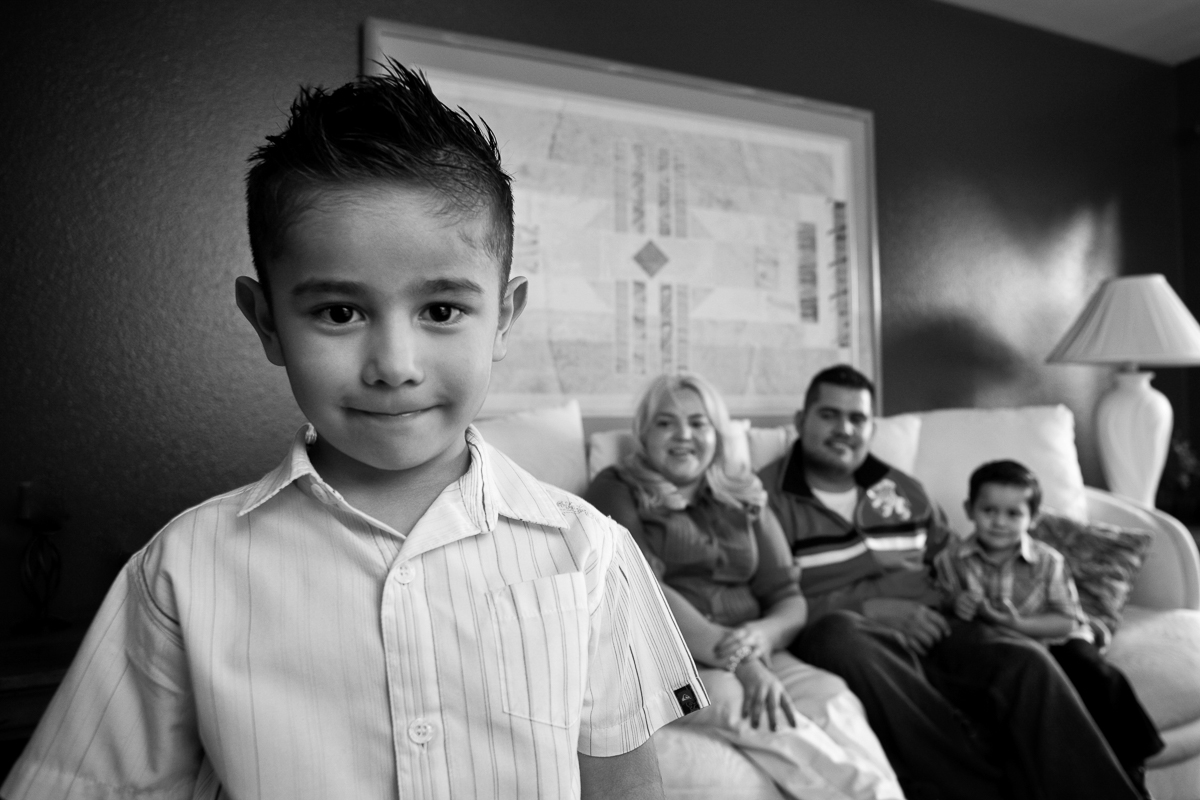 Hispanic boy with family in background