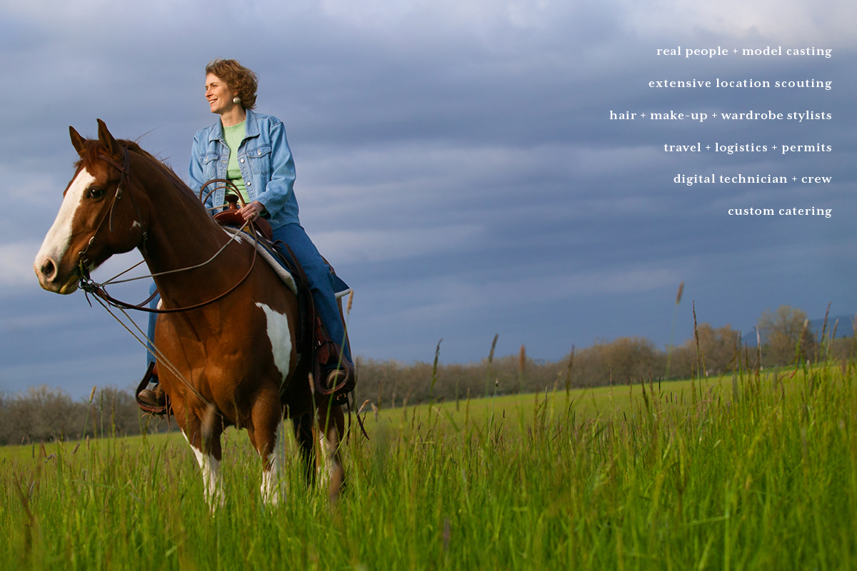 Middle aged woman on a horse in a green field with Spring clouds behind